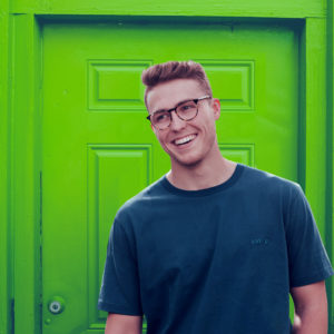 laughing man in front of a green door